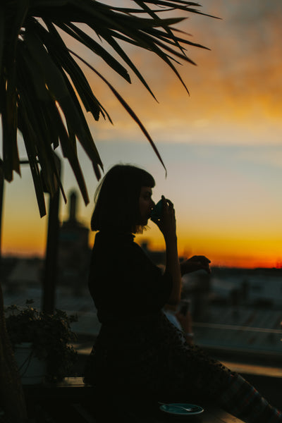 Woman drinking coffee against the backdrop of sunrise