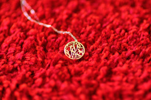 Arabic calligraphy circular pendant, sterling silver with silver chain on red fur.