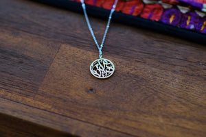 Arabic calligraphy circular pendant, sterling silver with silver chain on wooden table.