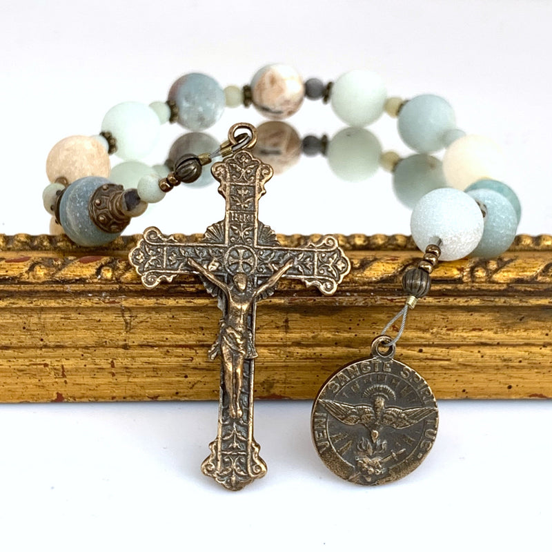Rosary with Holy Spirit bronze medal on right, Sacred heart crucifix on left with Amazonite Ave Maria beads in background.