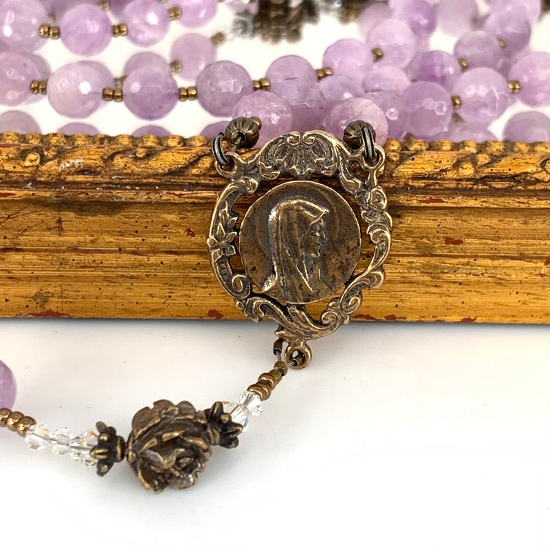Graceful bronze center with profile of our lady.  Amethyst rosary beads in background.  Pretty bronze rose bead and crystal spacers.