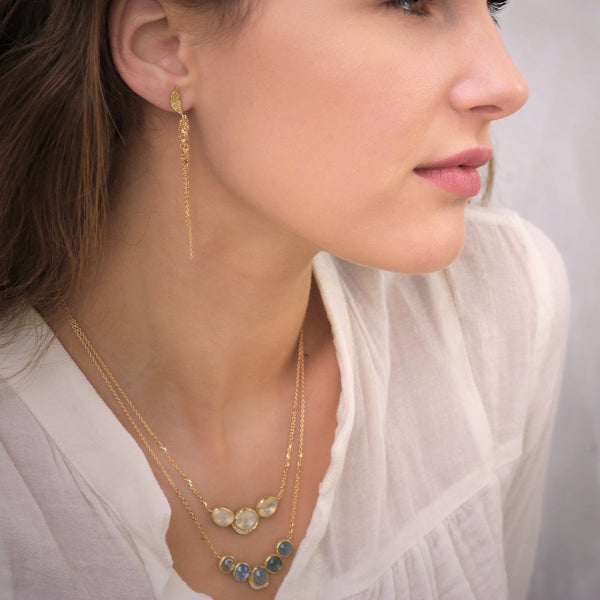 Model wearing Hand made in London Brooke Gregson 18k gold carved leaf earrings with 18k woven gold chain  Edit alt text