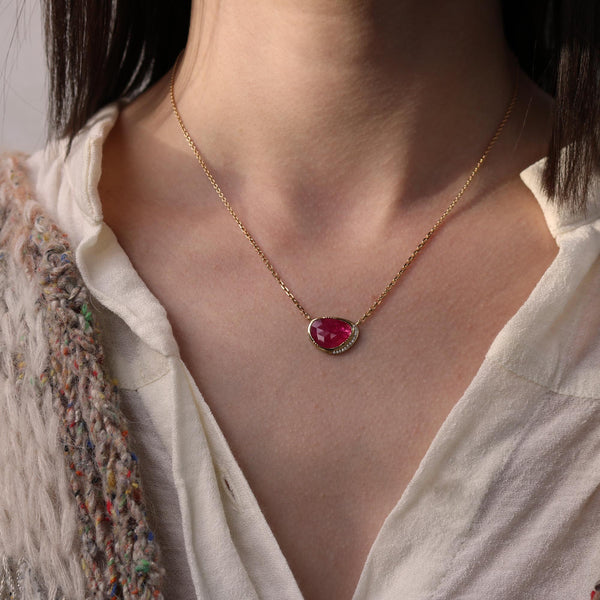 Model wearing Brooke Gregson 18k gold ruby necklace with diamond detail hand made in London
