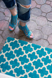 A teal doormat with a crosscross white Moroccon style print with a woman standing next to it.