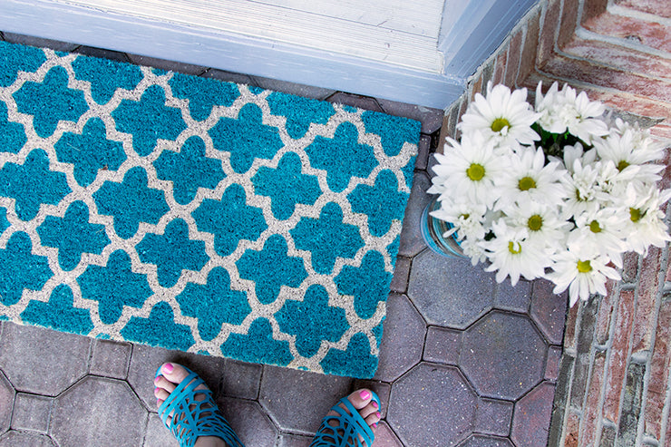 A teal doormat with a crosscross white Moroccon style print and a bouquet of flowers at the corner.