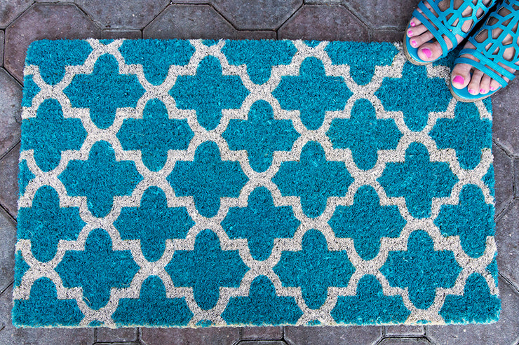 A teal doormat with a crosscross white Moroccon style print with a woman's feet on it in one corner.