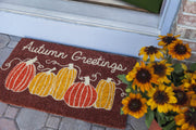 Coir doormat outside door with pumpkins illustration and Autumn Greetings text