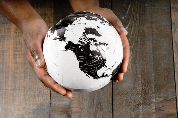 Image of two hands holds a black and white globe
