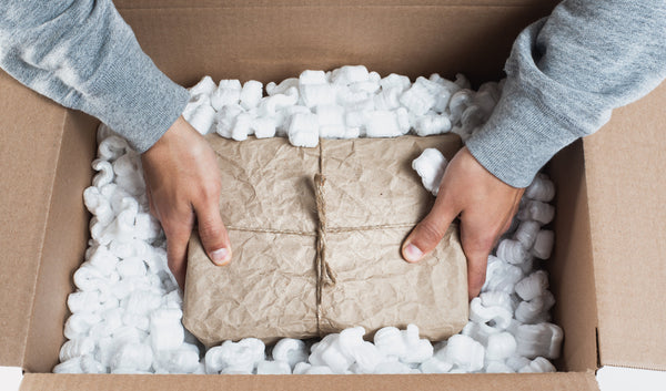 An image of two hands placing a brown wrapped package in a brown box filled with white styrofoam peanuts