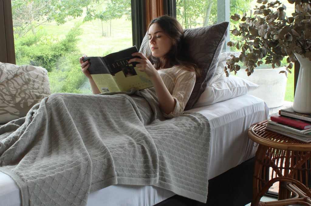 A cosy picture of a woman relaxing in bed with a book and the story grey pure alpaca wool blanket in triangle pattern.