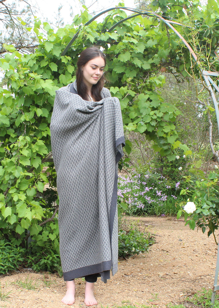 Woman in the garden wrapped in the mosaic pattern pure alpaca wool blanket. alpaca blanket in light grey and charcoal colors.