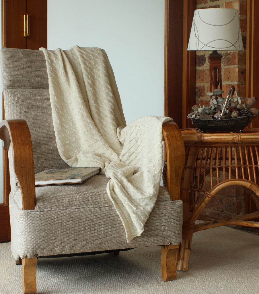 Beautiful pure alpaca wool blanket in triangle pattern in natural color draped over a chair.