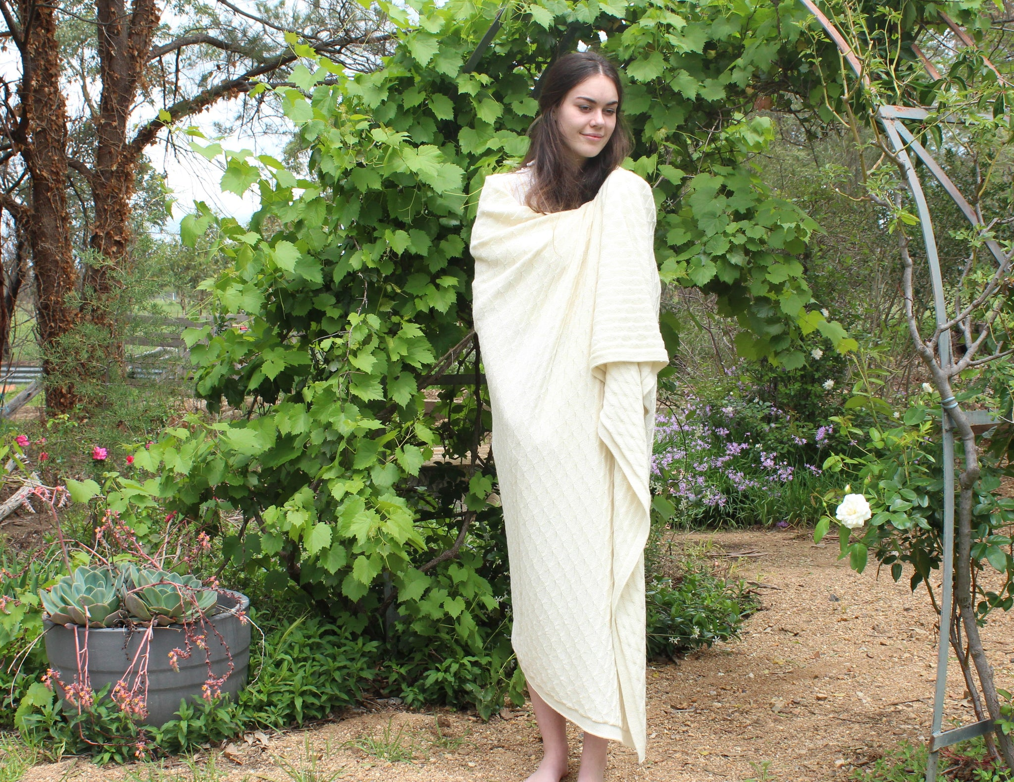 Woman wrapped in natural pure alpaca wool blanket in triangle pattern.