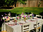 Load image into Gallery viewer, Beautiful summery table, complete with jewel coloured champagne glasses, blush linen napkins, candlesticks, coloured candles, bud vases, placemats and a fish bottle.