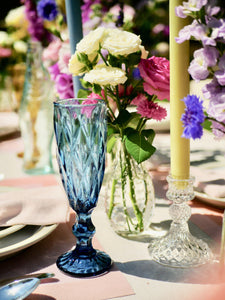 Blue champagne glass, bud vase, glass candlestick and avocado green candle. Treat Yourself Tablescape.