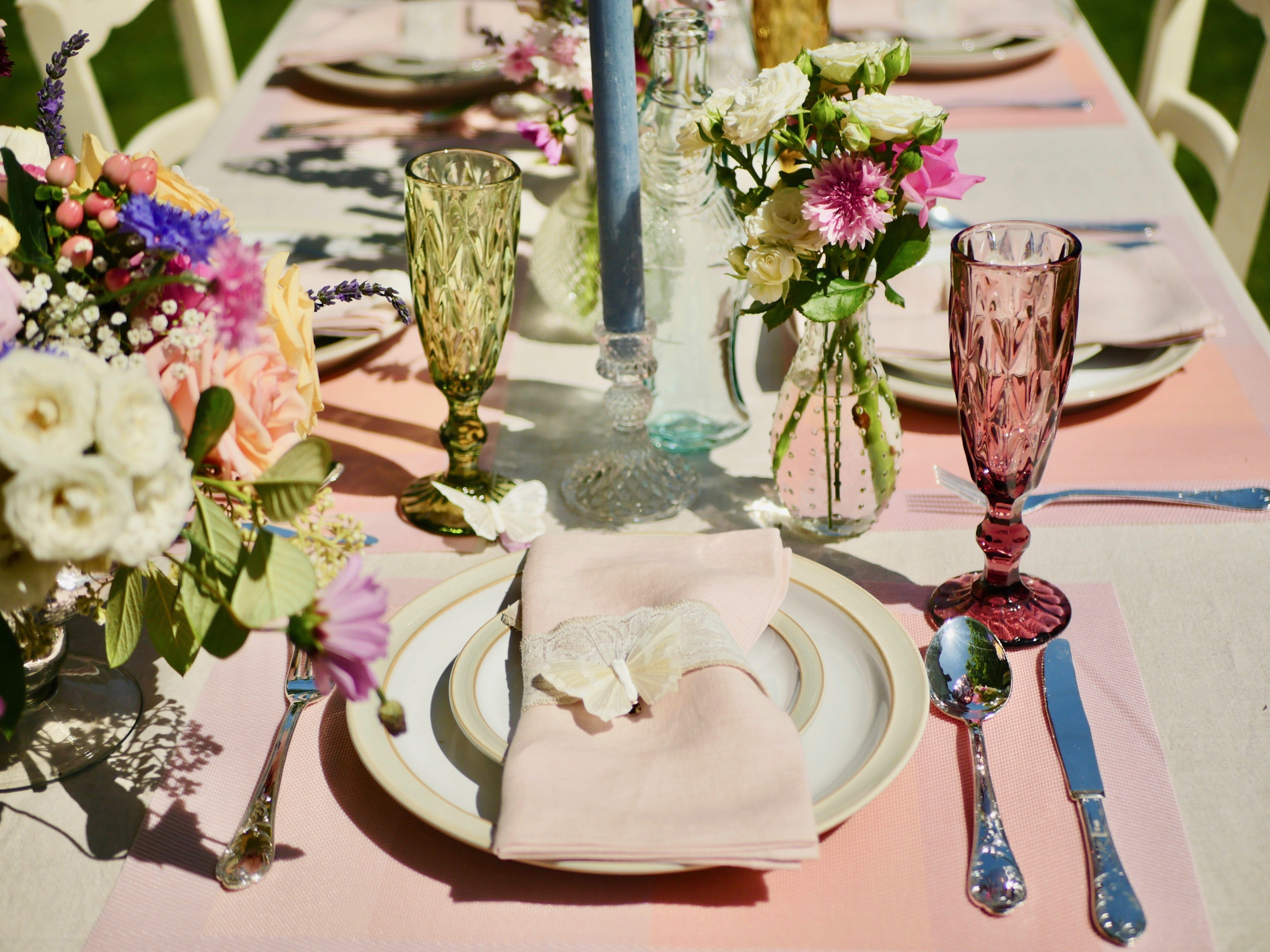 Beautiful summery table, complete with jewel coloured champagne glasses, blush linen napkins, candlesticks, coloured candles, bud vases, placemats and a fish bottle.