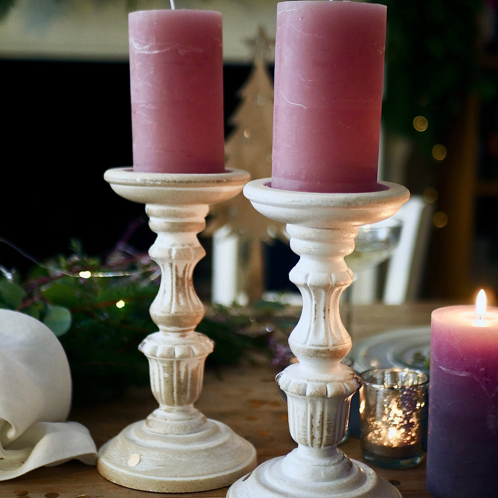 White wooden pillar candle holders with pink pillar candles at Dress For Dinner