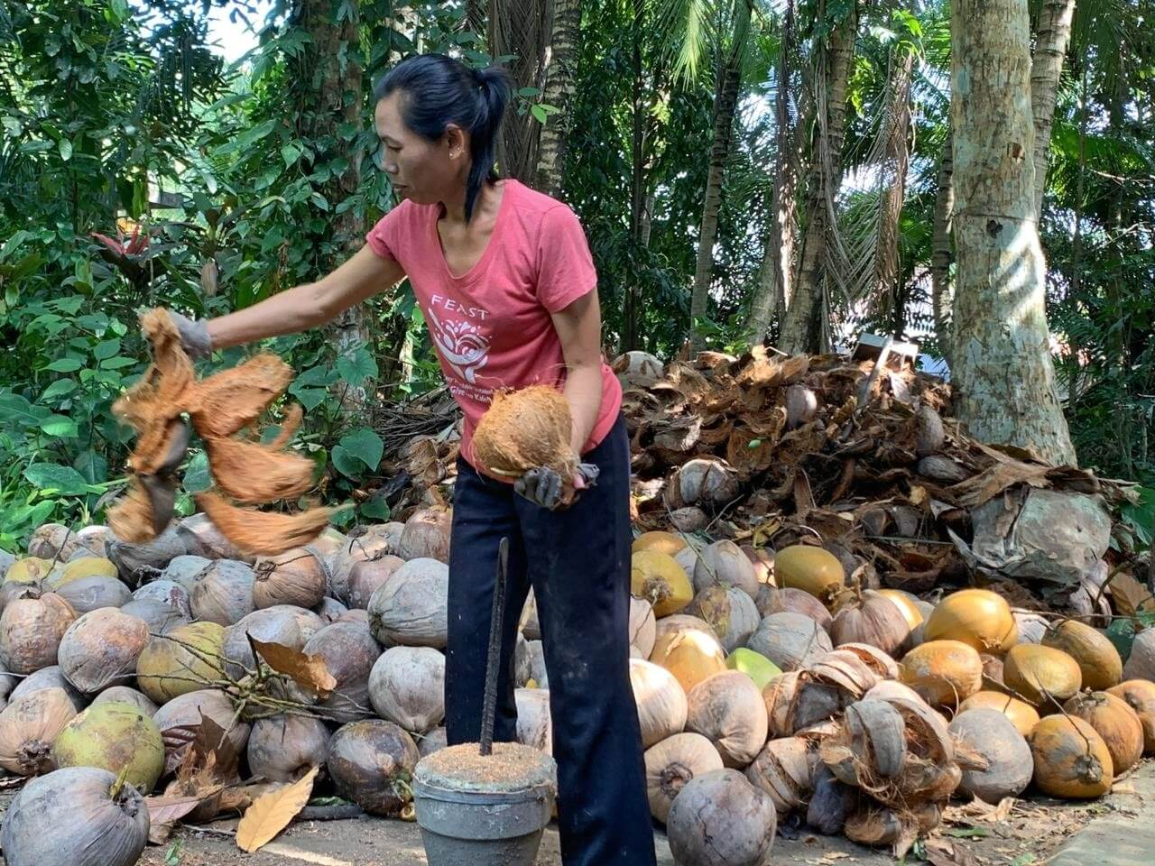 Indonesian woman working with coconuts