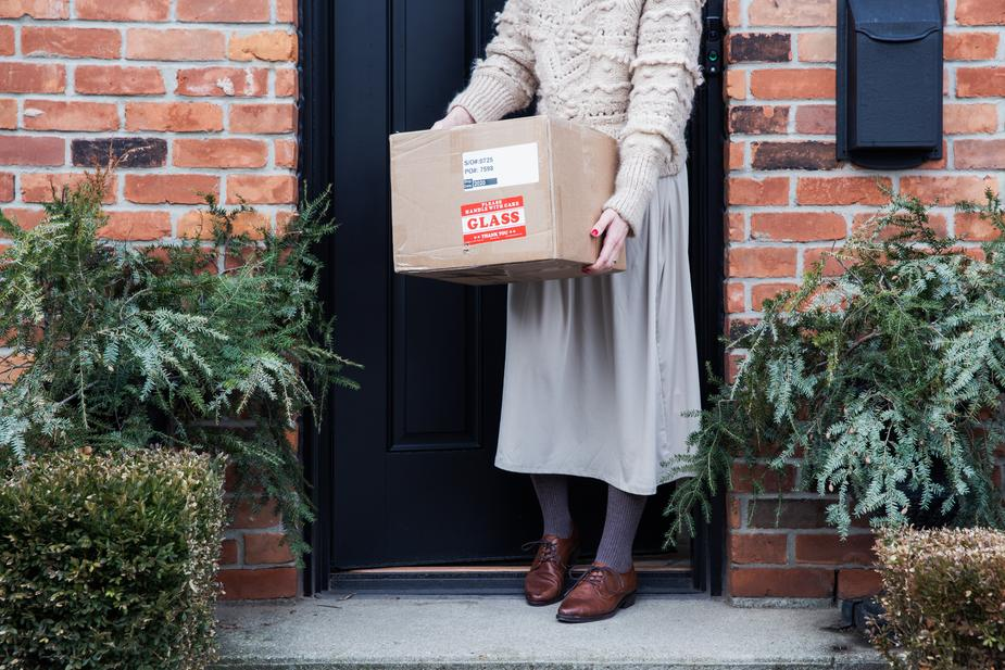 Woman with package just delivered in front of her door