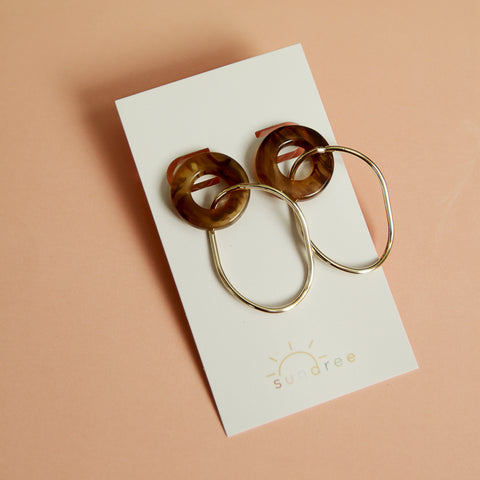Daylight Savings Drops - Brown Tortoise And Gold Drop Earrings - Flat Lay On Card Pink Background | Sundree Accessories