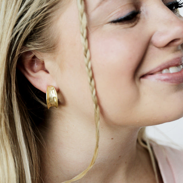 Wash And Fold Hoops - Matte Gold Hammered Hoop Earrings - Model Smiling | Sundree Accessories