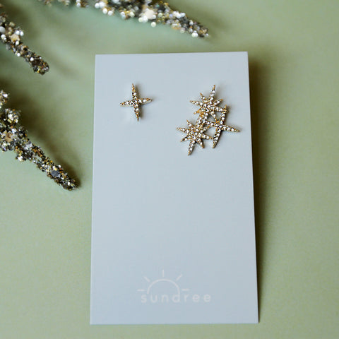 Help Me... I'm Feeling Studs - Asymmetrical Twinkling Star Stud Earrings - Flat Lay On Earring Card | Sundree Accessories