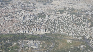 AJ4K_043 - Aerial 4K footage of Jerusalem: a long shot of the city of Jerusalem: The Knesset building and government Hill in the forground, west Jerusalem and east Jerusalem in the background