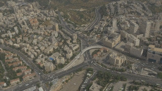 AJ4K_059 - Aerial 4K footage of Jerusalem: the city entrance: The Calatrava string bridge, central bus station and the Binyanei Ha'uma convention center, opening up to the west