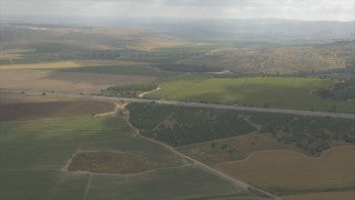 AJ4K_074 - Aerial 4K footage of Jerusalem: Road 1 in central Israel with green fields