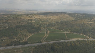 AJ4K_075 - Aerial 4K footage of Jerusalem: Road 1 in central Israel with green fields and the Judaean Hills in the background