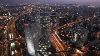 AT_016E Aerial helicopter footage of Tel Aviv circling Azrieli Towers and cityscape at sunset