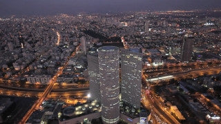 AT_017E Aerial helicopter footage of Tel Aviv Azrieli Towers and skyline at night