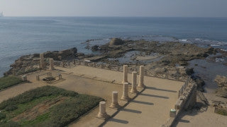 DC4K 005 G Aerial drone footage of the ancient Caesarea ancient harbor, flying west toward the sea.