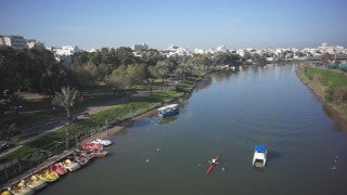 DC008B Aerial drone footage of Tel Aviv & Central Israel: Tel Aviv - low altitude above Hayarkon river with boats and birds, flying west