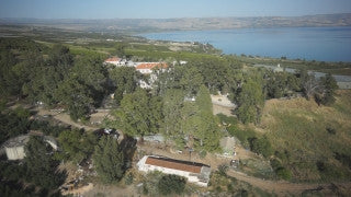 DN005B Aerial drone footage of the Sea of Galilee & Northern Israel: slow left turn flying above fields, orchards, buildings near Sea of Galilee with Golan Heights in background