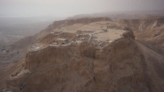 DS026B Aerial drone footage of Masada and the Dead Sea: Judean Desert - slow tilt from vertical top view to horizontal view of desert landscape