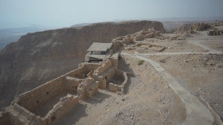 DS009B Aerial drone footage of Masada and the Dead Sea: low altitude flight above Masada and 360 degree shot of Judean Desert, end on mountain top