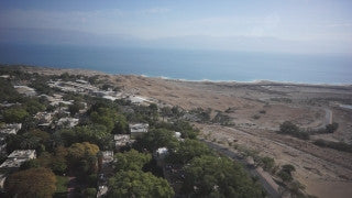 DS017B Aerial drone footage of Masada and the Dead Sea: Low altitude flight above Kibbutz Ein Gedi towards Dead Sea