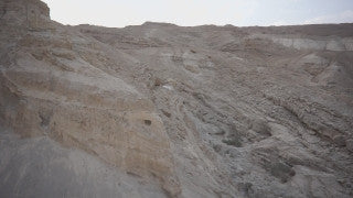 DS023B Aerial drone footage of Masada and the Dead Sea: Judean Desert - dolly in along cliff over mountains and creeks