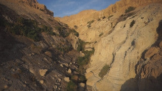 DS025B Aerial drone footage of Masada and the Dead Sea: Judean Desert - slow dolly in creek to reveal mountains at magic hour
