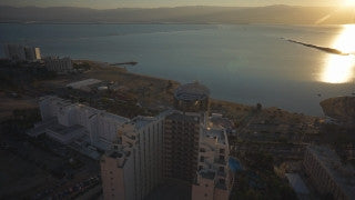 DS041B Aerial drone footage of Masada and the Dead Sea: Dead Sea - hotels in Ein Bokek by the Dead Sea at sunrise flying east to west