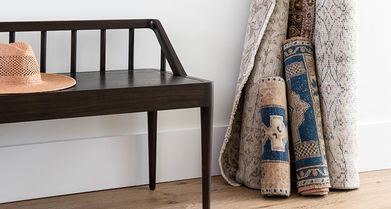 black wood bench and a collection of vintage rugs