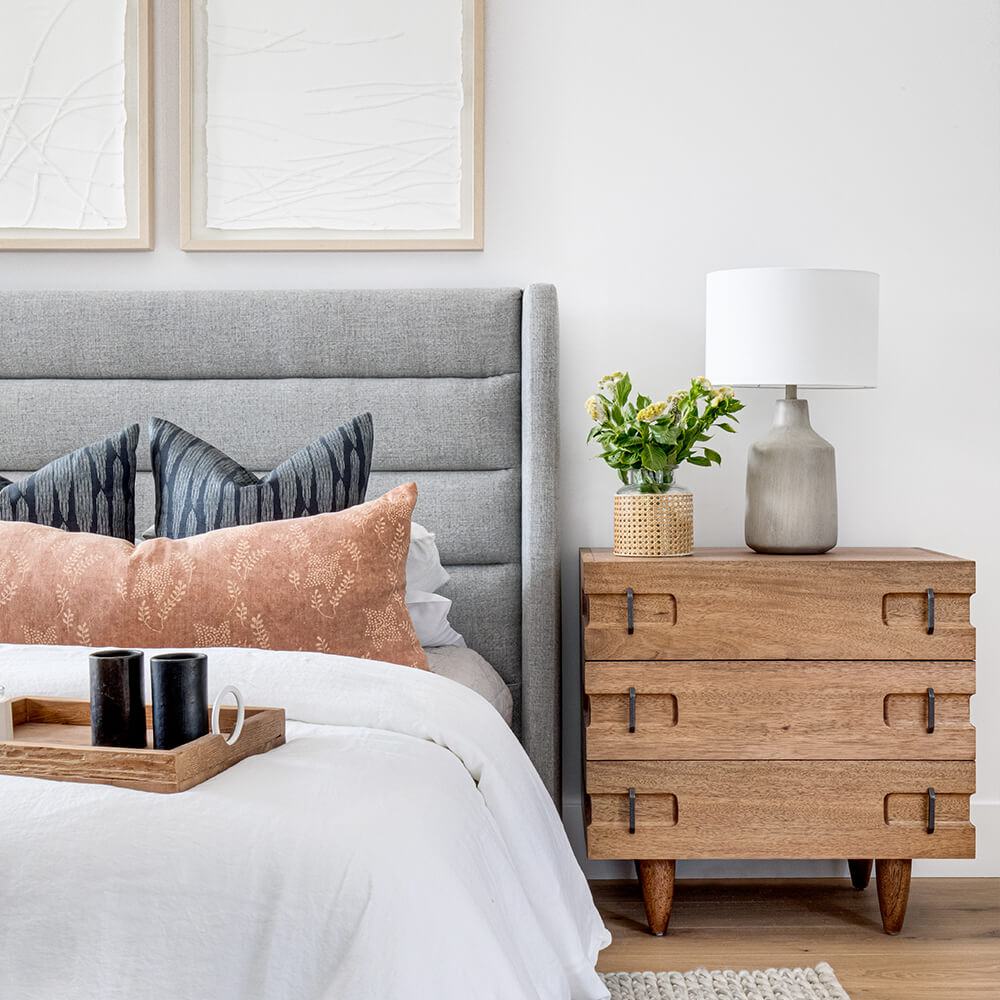 Photo of a coastal contemporary bedroom featuring a bed with a gray tufted headboard, a white duvet, and wood nightstand.