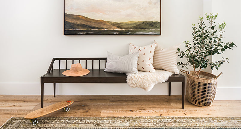 Coastal Scandinavian entryway with wood bench covered in pillows with a vintage rug on the floor