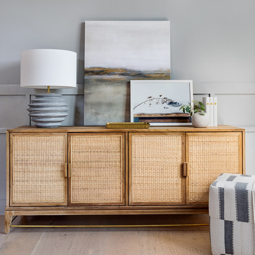 Teak credenza with cane doors holding a stylish vignette of decorative art objects and a table lamp