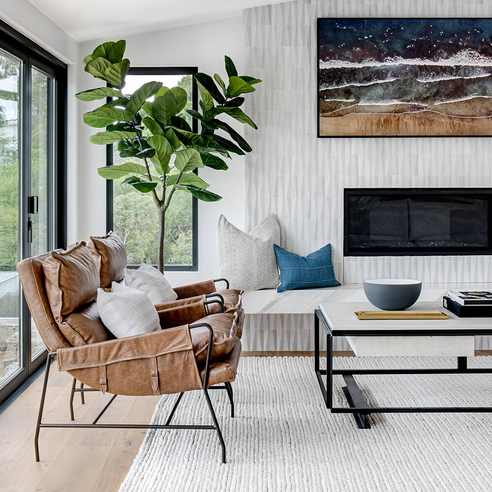 Mid-century meets California living room with leather lounge chairs and faux fiddle leaf tree