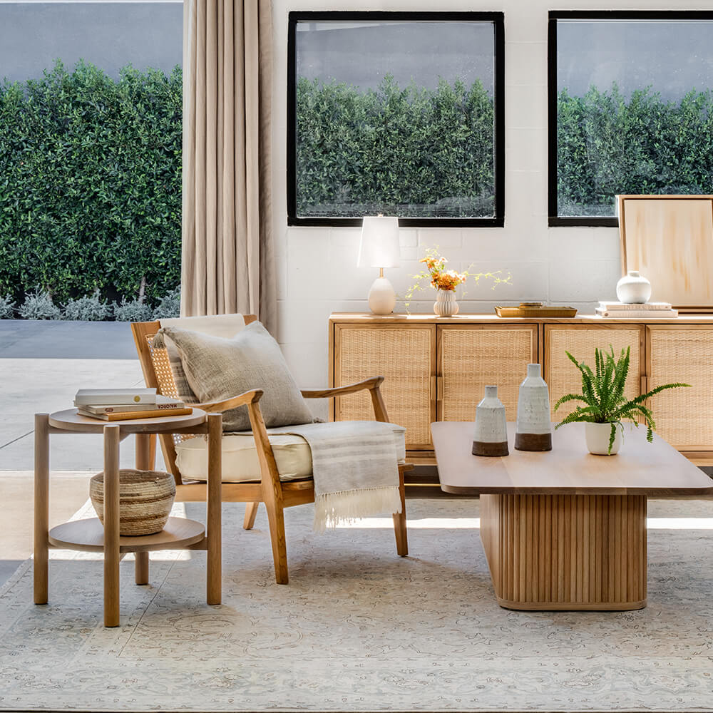 Oak Bay side table and Cape lounge chair designed by Lindye in a modern coastal living room