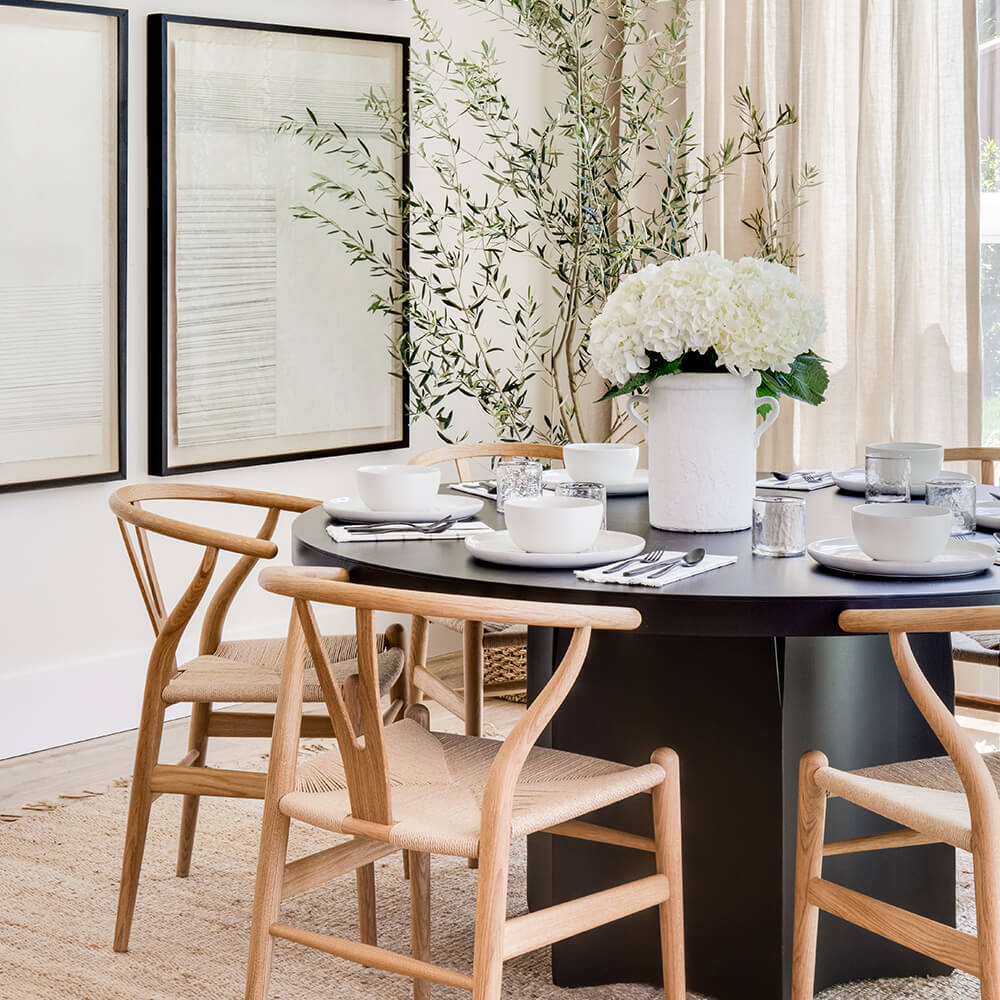 Coastal Scandinavian dining room with black round table