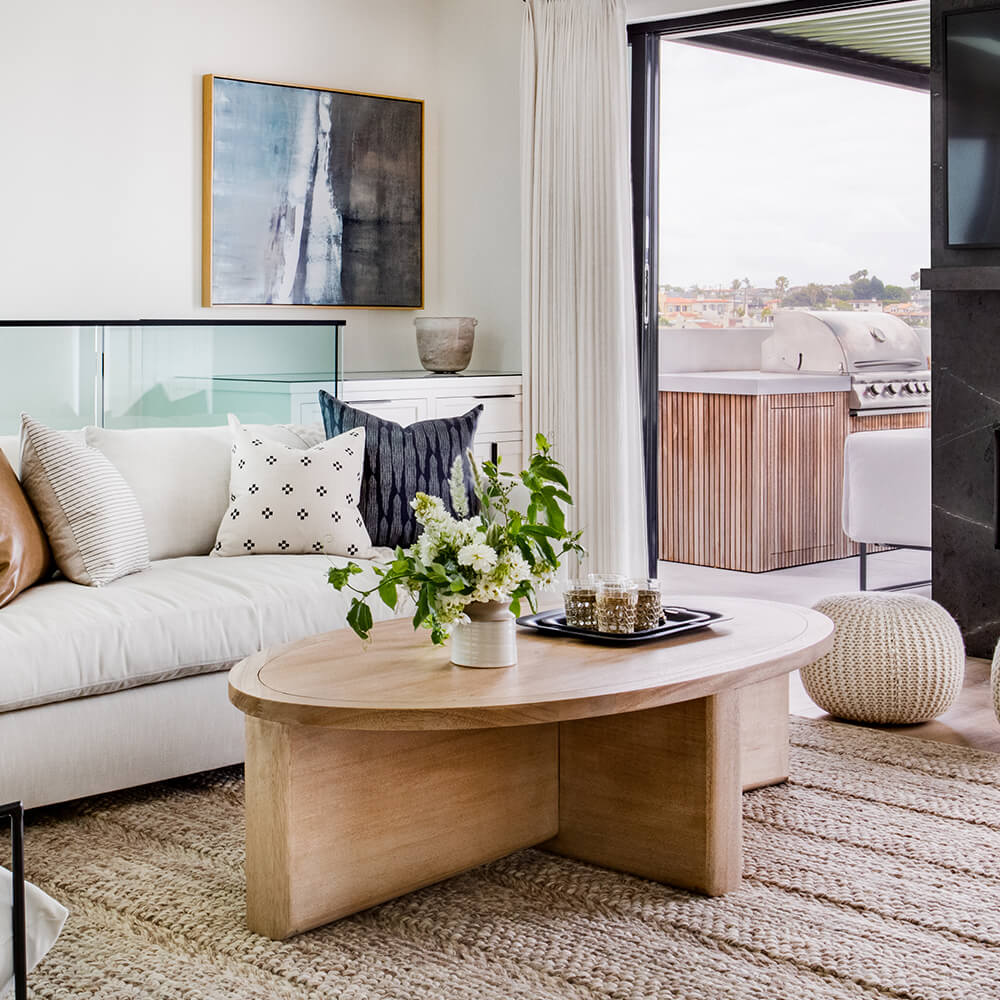Coastal cool living room interior design with oval wood coffee table and pouf