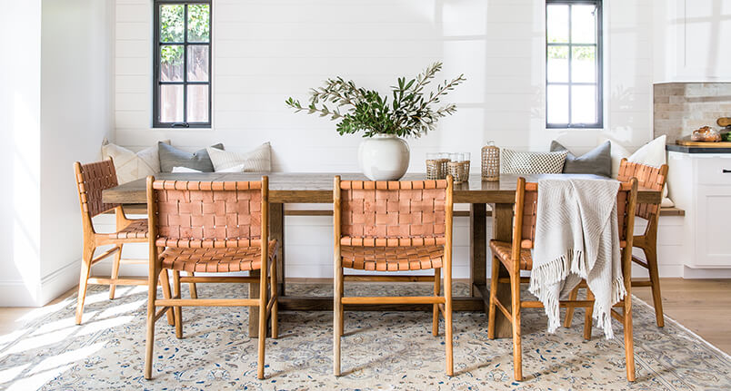 Cynthia tumblers and carafe on a modern farmhouse table with leather strap dining chairs on a vintage area rug